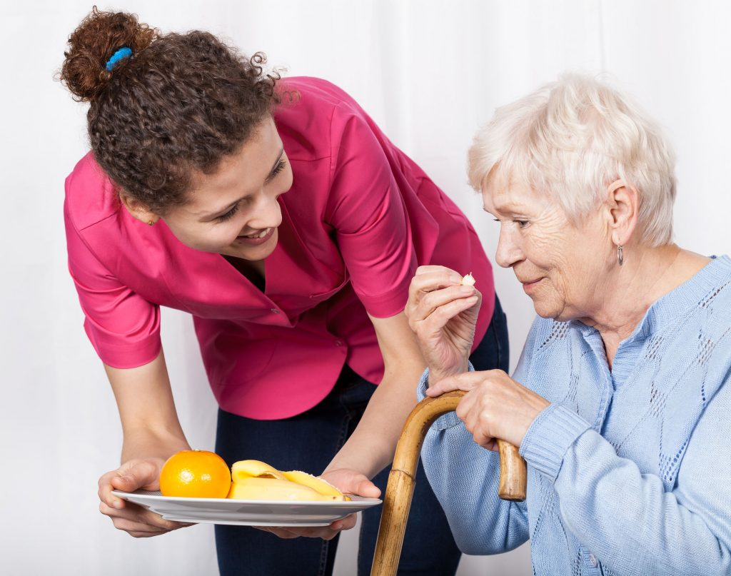older woman enjoying healthy snack from caregiver