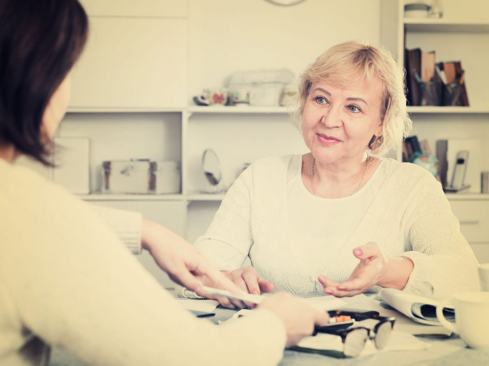a senior woman consulting a financial advisor for planning services