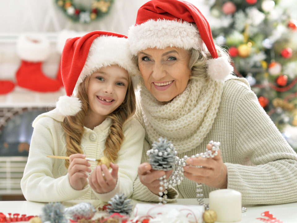 a senior woman and her granddaughter, wearing Santa hats and crafting