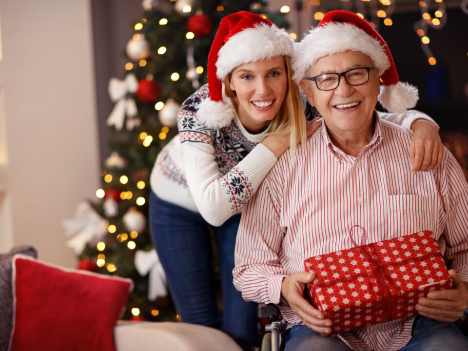 a senior man with his adult daughter, wearing Santa hats and holding a present in front of the Christmas tree