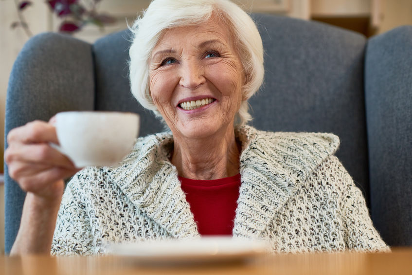 : a senior woman drinking coffee in her chair while wrapped in a warm sweater